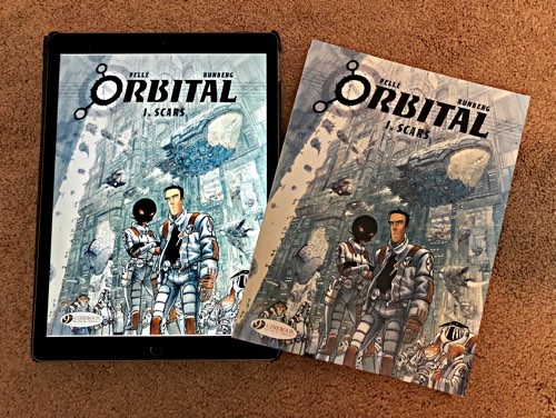 """Orbital v1 on the iPad 12"""". next to the print edition of the same book."""