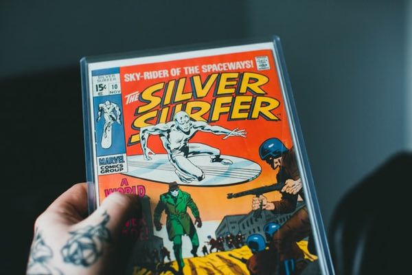 Man holding a Silver Surfer comic book in a mylar sleeve