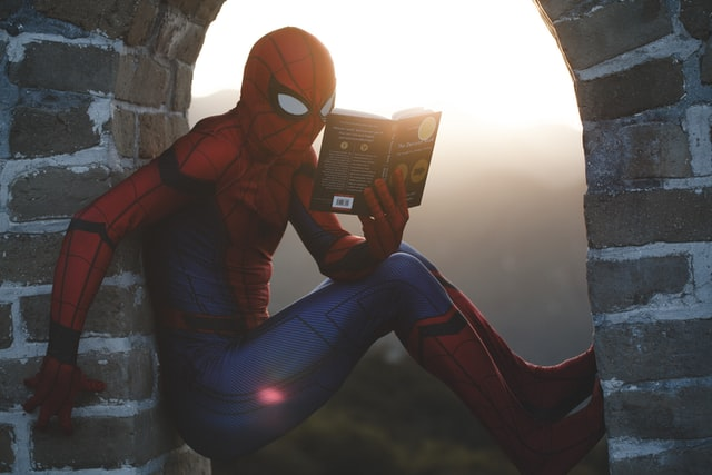 Spider-Man reading a book in a window